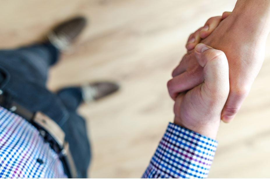 Foto de duas mãos firmando um acordo, representando o vendedor que reverteu o churn em vendas b2b